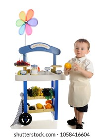 """A serious preschool """"vendor,"""" holding a lemon by his fruit stand.  The stand's signs are left blank for your text.  On a white background."""