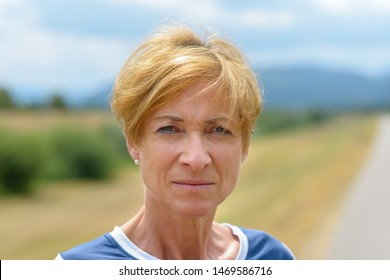Serious pretty blond middle-aged woman staring thoughtfully at the camera in a close up head shot on a quiet rural road in summer