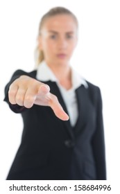 Serious pretty businesswoman pointing at camera on white background