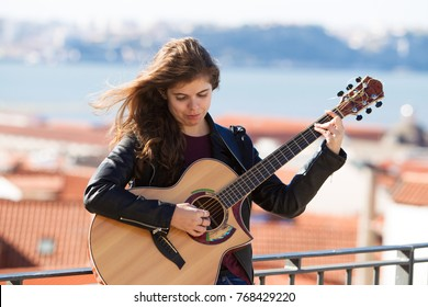 Serious Pretty Girl Playing Guitar on Rooftop