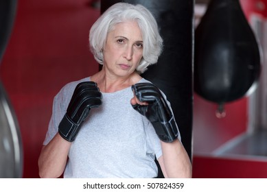 Serious pretty gray haired woman pretending  a boxer.
