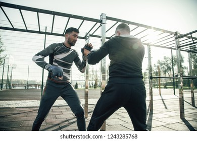 Serious professional MMA boxer having productive training and putting fists in boxing gloves up while looking at his trainer