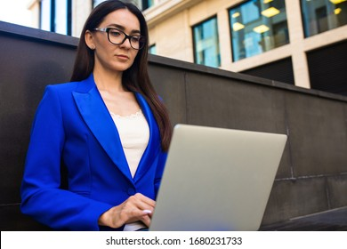 Serious proud female business worker online banking via laptop computer while sitting outdoors near enterprise. Woman jurist in suit and glasses using notebook