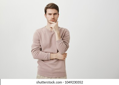 Serious puzzled handsome male model holding hand on chin as if thinking about something, squinting at camera with suspicious look and standing over gray background. Man decides what to buy