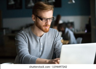 Serious red-haired male work at laptop sitting in café, focused millennial student study at computer, busy browsing internet in coffeeshop, concentrated guy surfing web chilling in coffeehouse