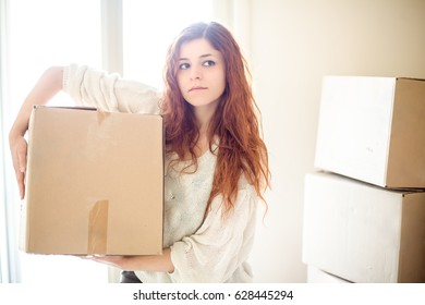 Serious Redhead Woman House Moving Holding a Box