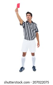 Serious referee showing red card on white background