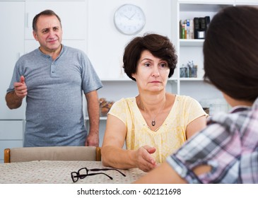 Serious retiree couple having conversation with adult daughter in home interior