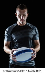 Serious rugby player holding ball against black background