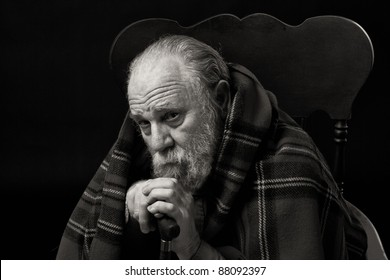 Serious sad old man in his seventies seated with a plaid shawl over his shoulders