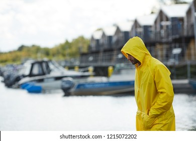 Serious sad young fisherman in yellow waterproof coat holding hands in pockets and looking down while moving along pier at seaport