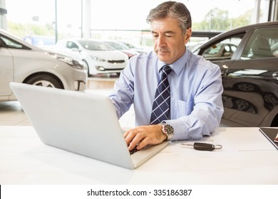 Serious salesman behind his desk at new car showroom