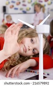 Serious school girl spinning model wind turbine in classroom