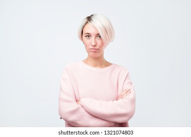 Serious self confident hipster girl in pink sweater posing with crossed hands