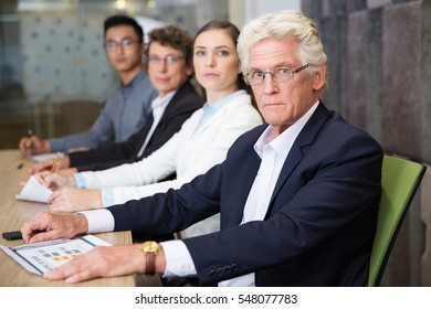 Serious senior businessman at meeting with team