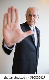Serious senior businessman showing stop gesture