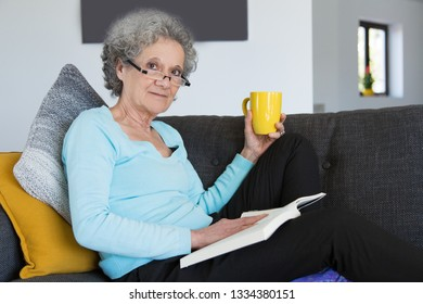 Serious senior lady suffering from joint pain and resting at home. Elderly grey haired woman sitting with book and warmer under knee. Sick concept