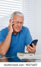 Serious senior man looking at calculator