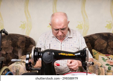 Serious Senior Man Looking Down at Spool of Red Thread and Threading Old Fashioned Manual Sewing Machine at Home in Living Room