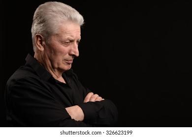 Serious senior man on a black background
