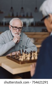 serious senior man playing chess in cafe and looking at opponent