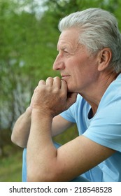 Serious senior man thinking in park on green background