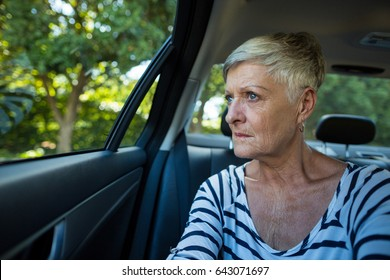 Serious senior woman looking through car window