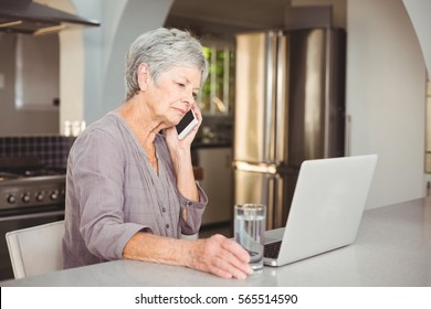 Serious senior woman talking on mobile phone while sitting in kitchen