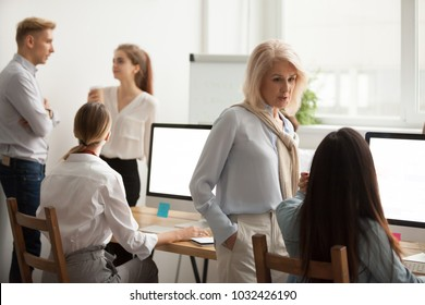 Serious senior woman talking to young employee discussing new idea in office, corporate team staff working together using computers and talking in coworking, colleagues collaborate, teamwork concept