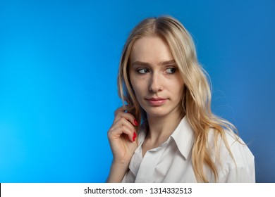 serious sensual blond transgender on blue background looking aside