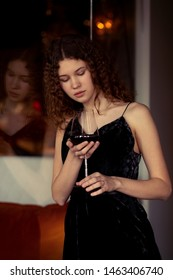 serious single luxury beautiful woman with wine standing near mirror, looking at wineglass