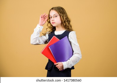 serious small girl wants to be teacher. hometwork. notebook for diary notes. study lesson. knowledge and education. Back to school. small girl with paper folder. Studying hard for good grades.
