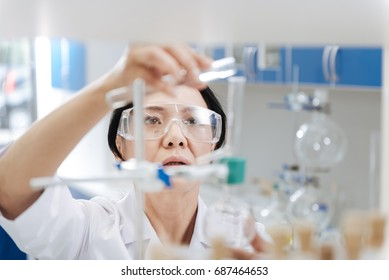 Serious smart woman holding a test tube