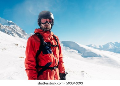 Serious snowboarder is standing in the red suit on the snow powder hill and looking into the distance
