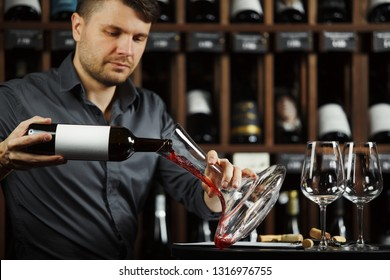 Serious sommelier pouring red wine in decanter
