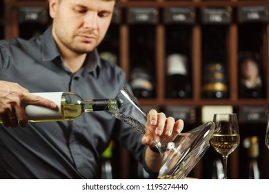 Serious sommelier pouring white wine from opened bottle in decanter to degustate and taste alcohol beverages, cellar full with containers collection having labels placed on shelves
