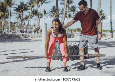 Serious sportive man supporting black woman doing deadlift with metal barbell standing on beach gym in sunlight.