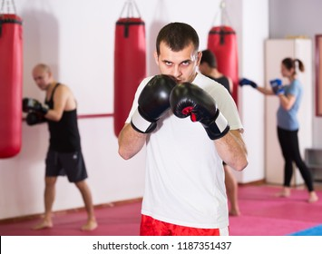 serious sportsman in the boxing hall practicing boxing punches during training