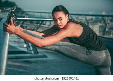 Serious sportswoman looking into the distance and pulling her leg with one foot on the banister