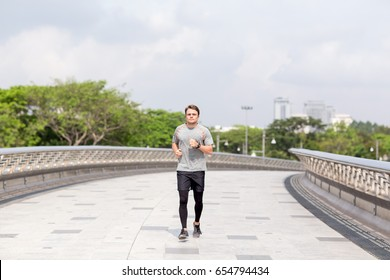 Serious Sporty Young Man Running on City Bridge