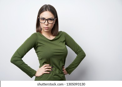 Serious strict woman in glasses standing looking at camera with intense look