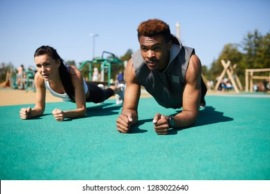 Serious strong tough young multi-ethnic couple doing plank at summer stadium and looking straight while training together outdoors