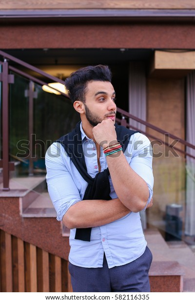 Serious student of Arabic businessman about something and remembers thinking, posing for catalog of brand of men's clothing, arranged meeting with friends, thinking where to go have fun on weekends