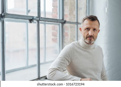 Serious stylish middle-aged man staring at the camera with a penetrating look as he leans against the sill of a large window