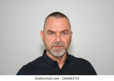 Serious stylish middle-aged man with a thoughtful expression staring directly at camera in a head and shoulder portrait over a grey studio background