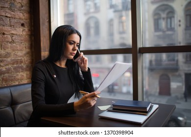 Serious successful business woman reading summary and talking with workers via mobile phone, sitting in restaurant in evening time. Female proud candidate reading summary during cellphone conversation