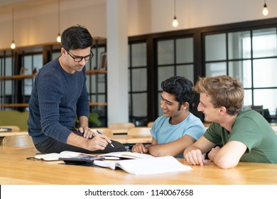 Serious teacher checking assignment of two students. Serious man in glasses pointing pen at notes of two cheerful guys. Education and internship concept