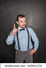 Serious teacher man threaten by finger on blackboard background