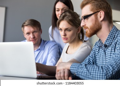 Serious team leader explains new online project on laptop to colleagues, focused coworkers group planning work listening to female boss analyzing data, business coaching, mentoring teamwork concept