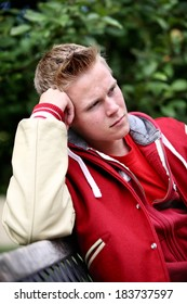 Serious teenage boy sitting on a bench outdoors